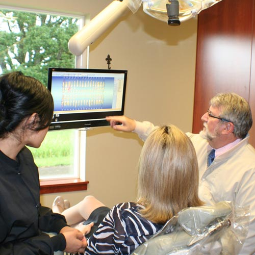 Kendall F. Horn, D.M.D., dental assistant, and patient reviewing digital tooth records